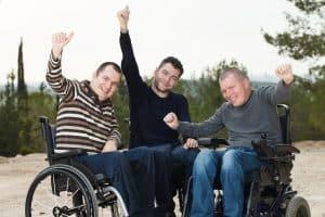 three happy males on wheelchair