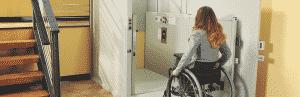 executive woman on wheelchair entering vertical platform lift
