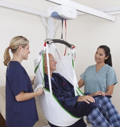 man on ceiling lift being helped by two health professionals
