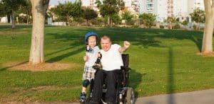 wan on wheelchair hugging boy on rollerblades in a park