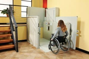 woman in wheelchair using indoor vertical platform lift at bottom of stairs