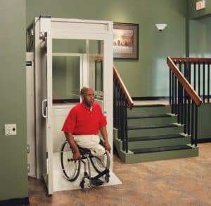man in wheelchair using vertical platform lift