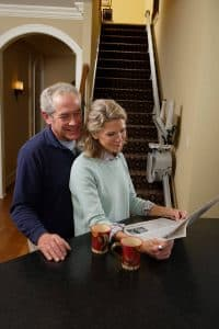 Senior couple reading newspaper with folded stair lift in background
