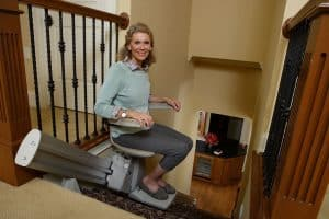 Senior woman smiling while seated stair lift