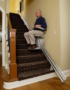 man seating stair lift middle of staircase