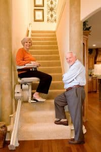 senior couple looking at camera while woman is seated on indoor straight stair lift