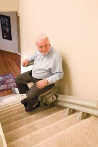 man using stair lift middle of stairs