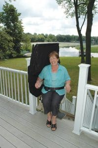 woman while seated on outdoor stair lift at top of stair