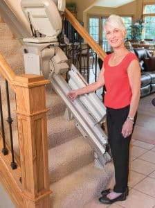 Senior woman at the top of stairs while stair lift is in middle of stairs