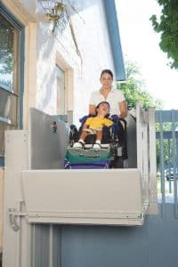 woman with child on wheelchair using outdoor vertical residential platform lift at top