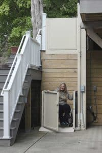 woman in wheelchair using outdoor vertical residential platform lift at bottom