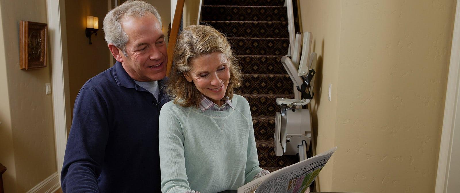 senior couple reading paper near stair lift