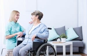 Senior woman on wheelchair and her caregiver
