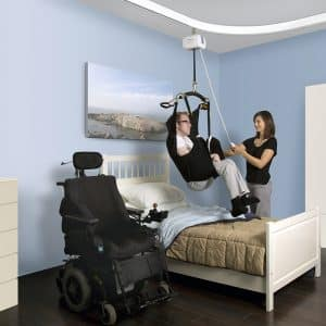 man using ceiling lift helped by caregiver with wheelchair next to the bed