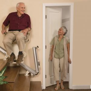couple smiling while man in seated on stair lift
