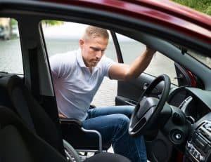 man on wheelchair entering car