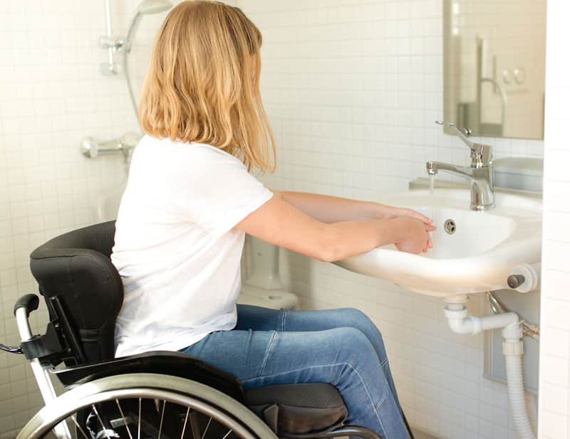 woman in wheelchair washing hand in bathroom